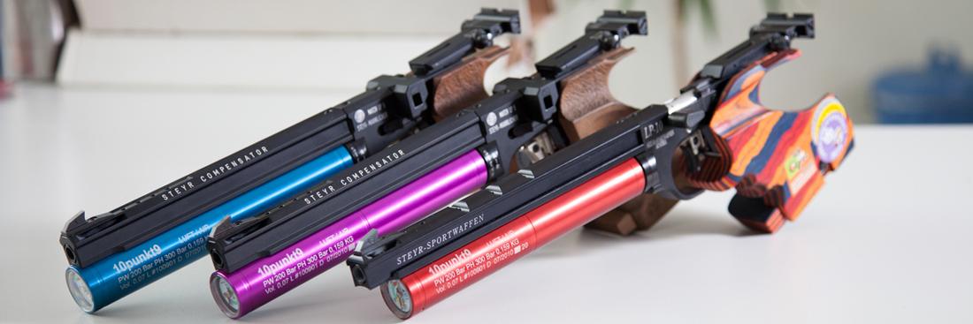 Laserbeschriftung auf drei Sportpistolen, die zuvor eloxiert wurden